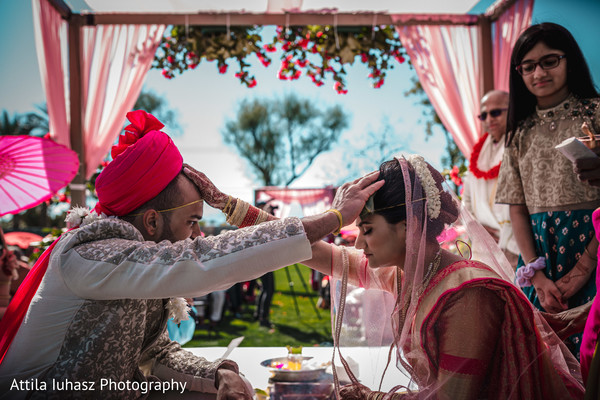 Indian couple putting hands on their foreheads.