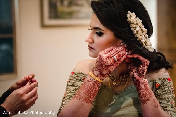 Indian bride putting earrings.