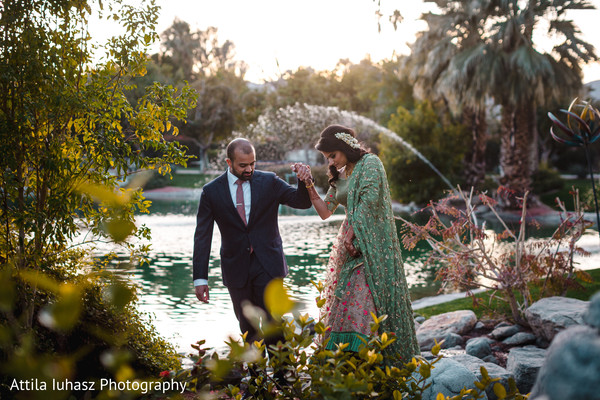Indian couple in formal wear walking by the lake.