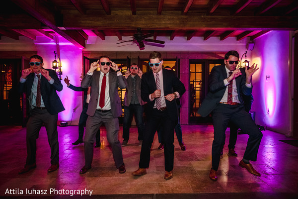 Indian groomsmen performing during reception.