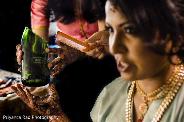 Indian bride being assisted by hair and makeup artist.