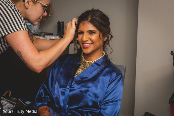 Maharani smiling at the camera while her make up is being done