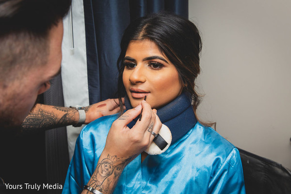 Indian bride getting her make up done