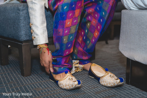 Indian groom getting his shoes on