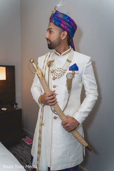 Indian groom in white posing with his wedding sword