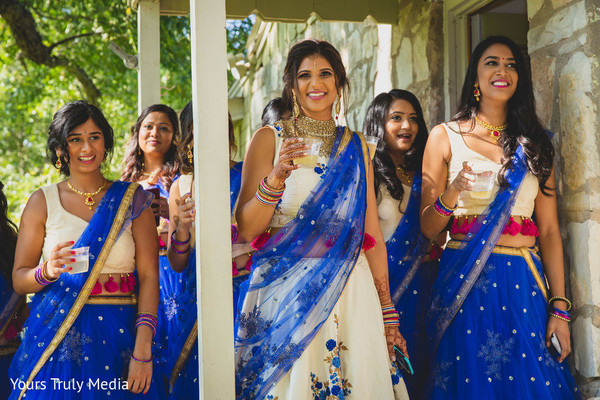 Indian bridesmaids sharing a drink with theIndian bride