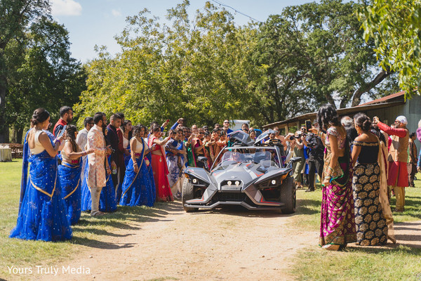 Indian newlywed couple leaving the wedding yard in a sports car