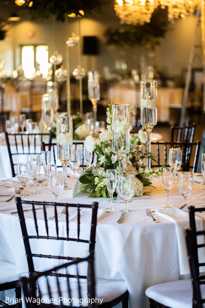 White decorations for Indian wedding reception tables.
