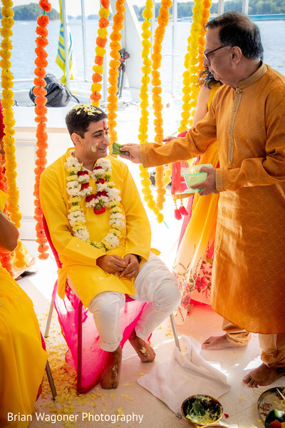 Indian groom getting all  smeared with yellow haldi.
