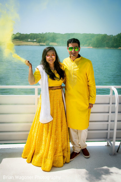 Indian bride holding a yellow smog stick next to groom.