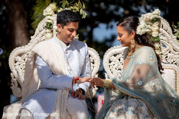 Indian bride putting wedding ring on groom.