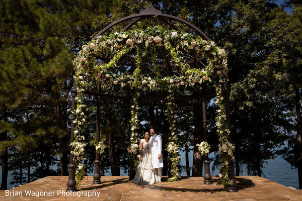 Indian couple posing under flower decorated mandap.