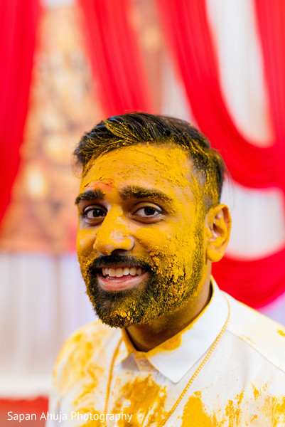 Tumeric paste all over Indian groom's face.