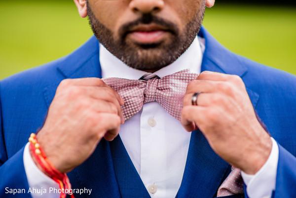 Indian groom tying his bow tie.
