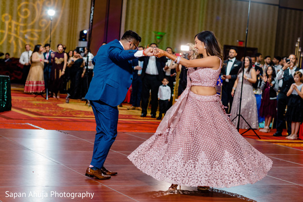 Indian couple dancing in front of the guests.