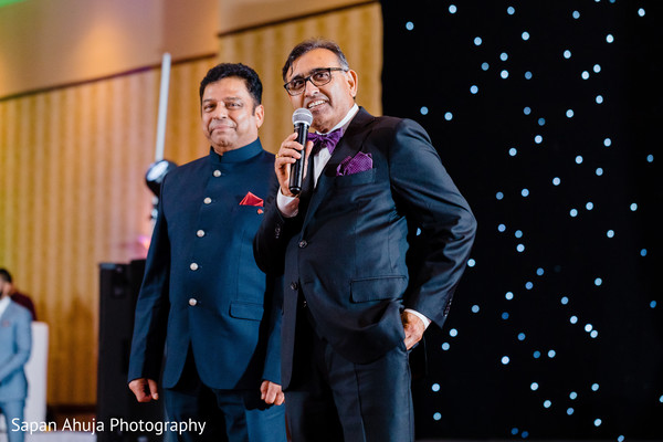 Indian relatives wearing suits during reception.