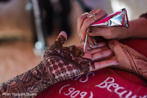 Indian bride getting her henna art on hands capture.