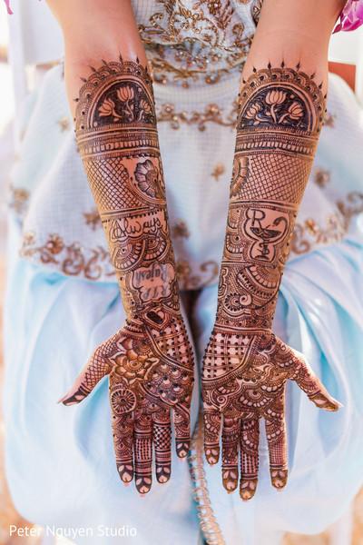 Maharani's brown henna art decor on hands.