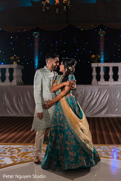 Indian bride and groom on their sangeet turquoise color outfits.