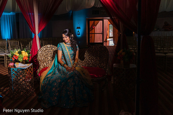 Indian Bride on her sangeet golden and turquoise lehenga.