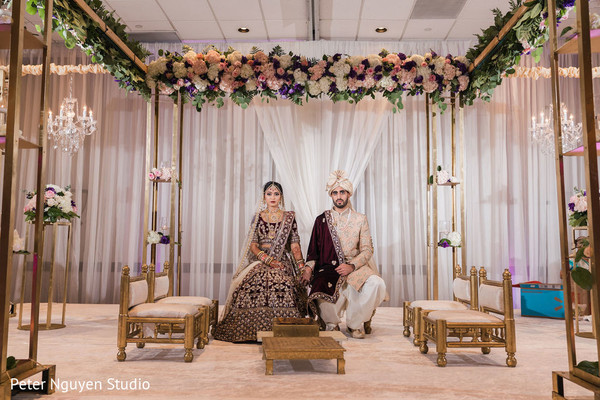 Indian bride and groom seating under the mandap.
