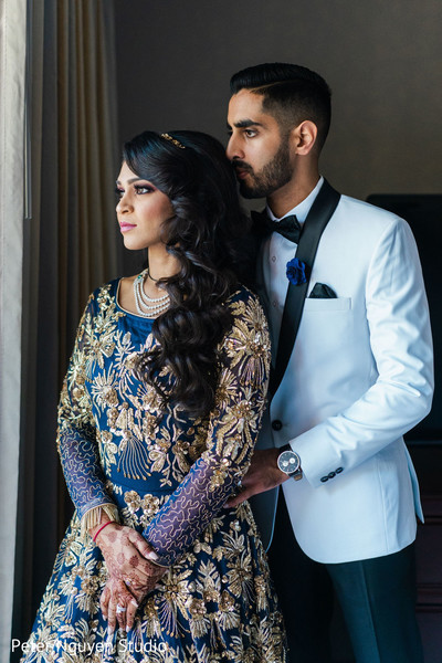 Indian couple in elegant reception outfits.