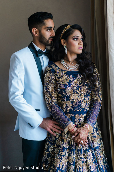 Indian couple standing in fabulous reception outfits.