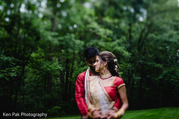 Indian groom in red hugging his Maharani from behind
