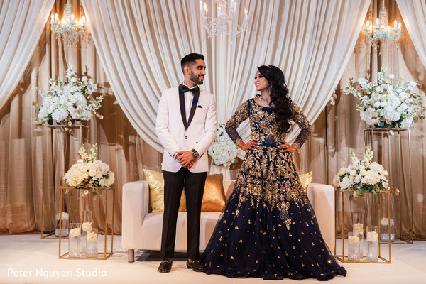 Indian couple exchanging glances in their reception stage.