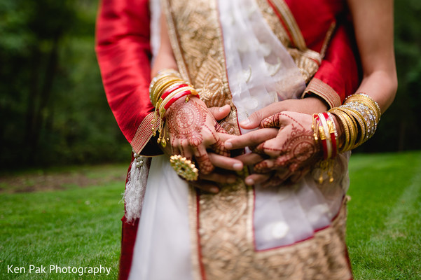 A close up of the Indian couple holding hands