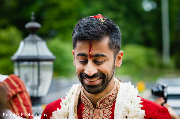 Indian groom in red with a red flower on his head