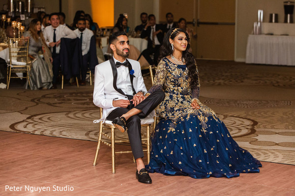 Indian couple enjoying reception performances.