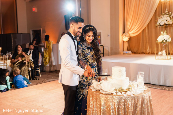 Indian bride and groom slicing their wedding cake.