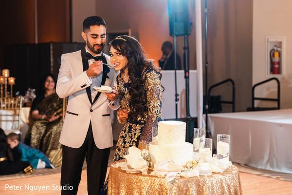 Indian couple sharing their wedding cake.