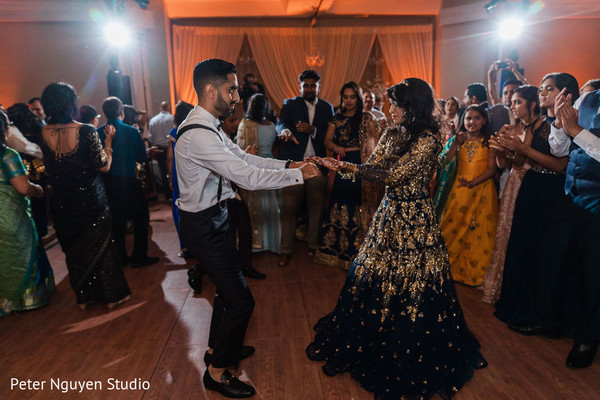 Indian bride and groom dancing at the tunes of the music.