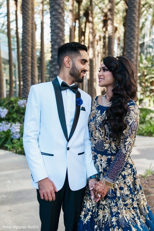 Indian bride on her  blue lehenga and groom with white suit.