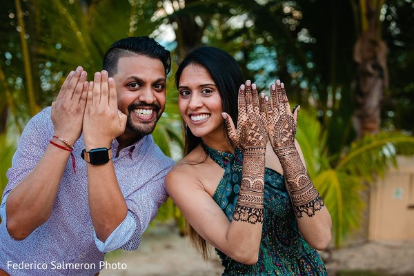 Indian bride and groom posing during mehndi party.