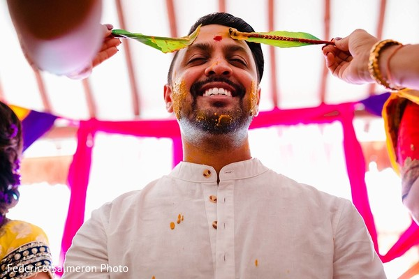 Indian groom being rubbed with turmeric paste