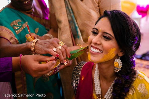 Indian bride being rubbed with yellow turmeric paste.