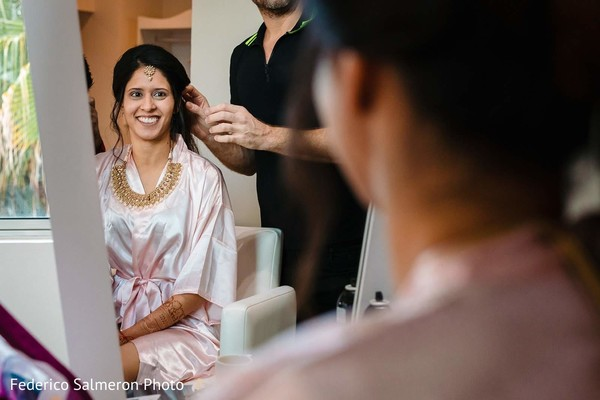 Indian bride having her hair done before the ceremony.
