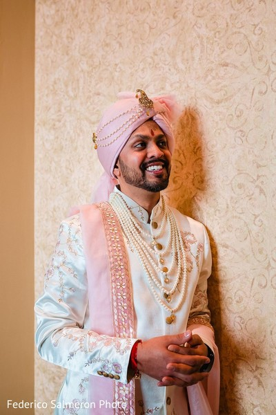 Indian groom white sherwani and pink jeweled turban.