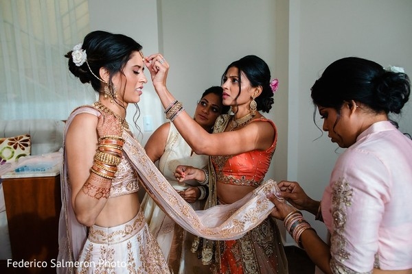 Indian bride being helped with her bridal look.