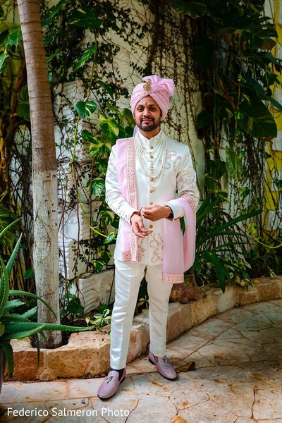 Indian groom in an elegant white sherwani and pink turban.