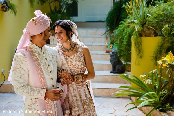 Indian couple on their white, pink and golden ceremony outfits.