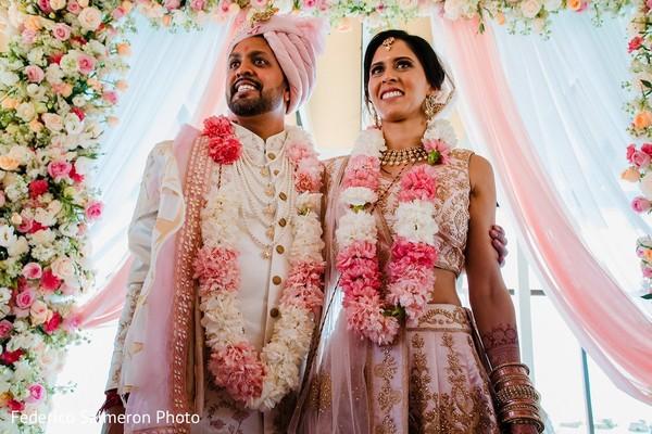 Indian bride and groom posing at wedding ceremony mandap.