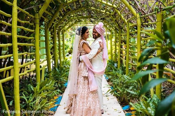 Indian couple posing at wedding venue garden.