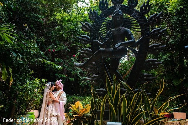 Indian couple posing next to Indian God garden statue.