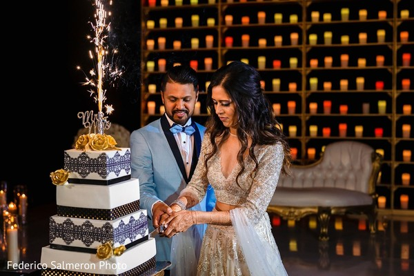 Indian newlyweds cutting the cake capture