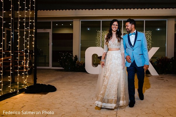 Indian couple at wedding reception entrance.