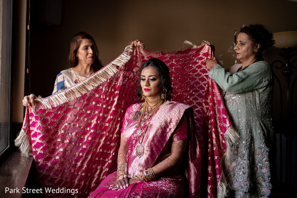 Indian relatives putting the veil on the Indian bride